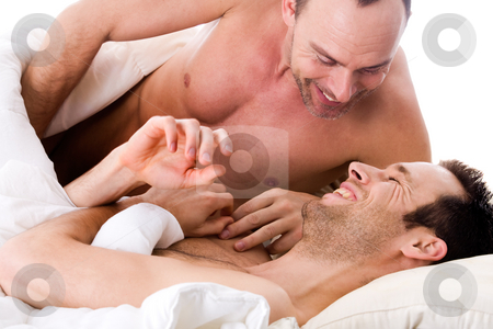 Smiling men couple in bed stock photo, Happy homo couple in a white bed taking care of his boyfriend by Frenk and Danielle Kaufmann