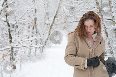 Winter landscape woman standing pensive in the snow stock photo, Woman standing pensive in the snow by Frenk and Danielle Kaufmann