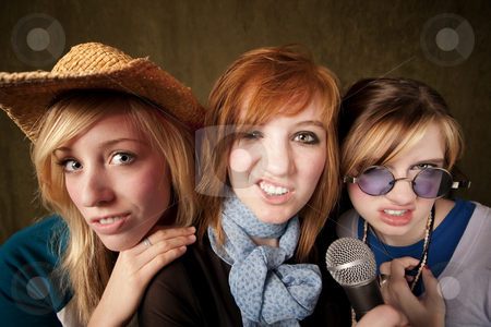 Three Young Girls with Microphone Making Faces stock photo, Portrait of three pretty young girls with a microphone making faces on green background by Scott Griessel