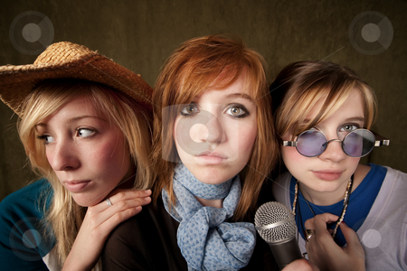 Three Young Girls with Microphone stock photo, Portrait of three pretty young girls with a microphone on green background by Scott Griessel