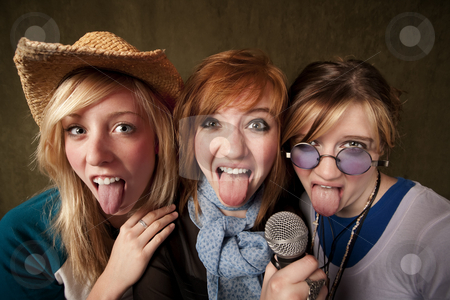 Three Young Girls with Microphone and Tongues Out stock photo, Portrait of three pretty young girls and tongues out with a microphone on green background by Scott Griessel