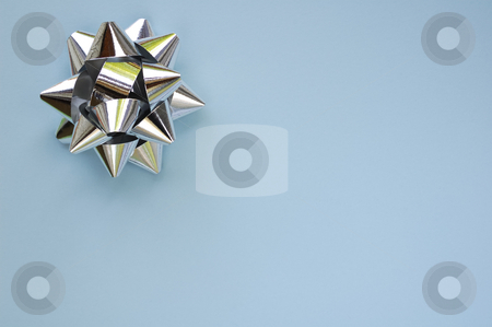 Star on pale blue stock photo, A decorative star, made from silver ribbon, on a plain, pale blue background with space for text (copy). by Alistair Scott