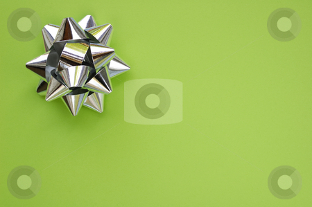Star on green stock photo, A decorative star, made from silver ribbon, on a plain green background with space for text (copy). by Alistair Scott
