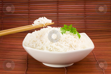 Bowl of rice on mat stock photo, Closeup of rice on chopsticks and a bowl on mat by Laurent Renault