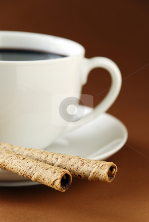 Black coffee and wafers stock photo, A cup of black coffee and chocolate cream wafers. Focus is on wafers. by Paul Turner