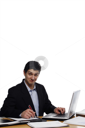 Smug Businessman stock photo, Businessman sitting at a desk with smug look on his face looking at the camera.  Vertical isolated on white. by Orange Line Media