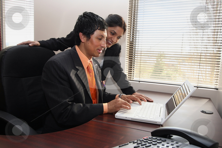 Business Team stock photo, Male and female business colleagues working together on a laptop and pleased with their progress by Orange Line Media