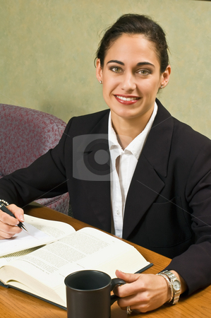 Businesswoman Looking into Camera - In Close stock photo, Young, seated businesswoman looking into camera. by Orange Line Media