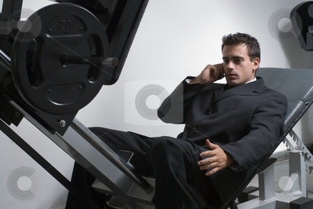 Businessman at the Gym stock photo, Handsome businessman, wearing a suit, talking on cellphone in the gym. by Orange Line Media