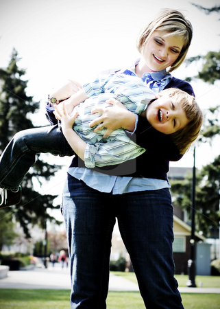 Mother and Son Playing Airplane stock photo, Cute young mother with her son in her arms flying him around. Vertical, high-contrast shot by Orange Line Media