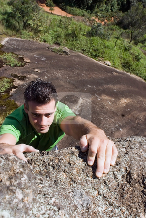 Man Rock-Climbing stock photo, Vertical shot looking down at an attractive man sticking to the edge of a rock wall with his fingertips by Orange Line Media