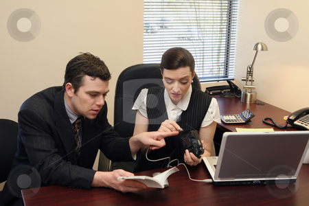 Digital Camera Setup - Confused Horizontal stock photo, Businessman and businesswoman setting up a new digital camera. by Orange Line Media