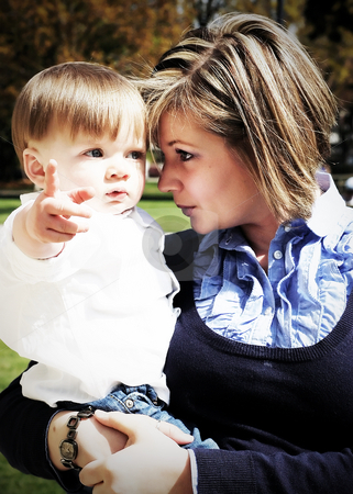 Mother and Son stock photo, Adorable young boy pointing at something while being cradled in his mother's arms. Vertically framed high-contrast shot by Orange Line Media