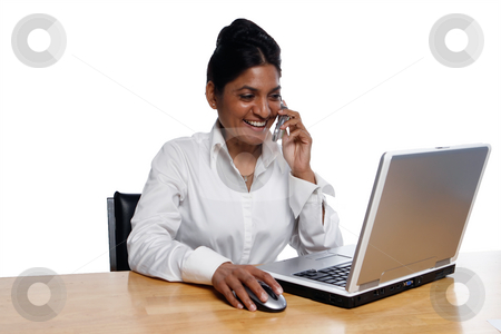 Businesswoman at Desk Multitasking stock photo, Isolated smiling businesswoman sitting at a desk using a laptop and talking on a cellphone by Orange Line Media