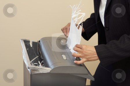 Paper Jam? stock photo, Close-up of a woman shredding a piece of paper in an office shredder by Orange Line Media