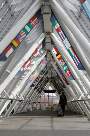 Businesswoman in Walkway - Vertical Shot stock photo, Businesswoman walking through a walkway / skybridge pulling her luggage behind her. The walkway is lined with flags. Vertically framed shot with the woman walking away from the camera. by Orange Line Media