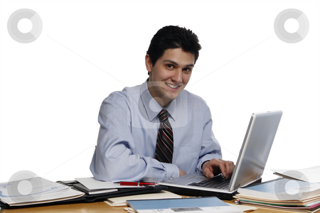 Working for You stock photo, Businessman leaning over desk towards a laptop smiling at the camera.  Shot horizontal isolated on white. by Orange Line Media