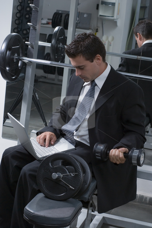 Working and Lifting stock photo, Young businessman doing biceps curls while working on his laptop by Orange Line Media