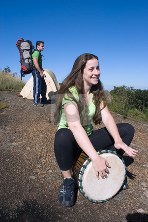 Couple Camping stock photo, Vertically framed shot of a young couple on a camping trip. He has his backpack on in the background and she is playing a bongo drum. Set against a clear blue sky by Orange Line Media