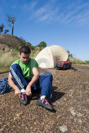 Man Putting on Climbing Shoes stock photo, Attractive young man putting on his rock-climbing shoes in front of his tent by Orange Line Media