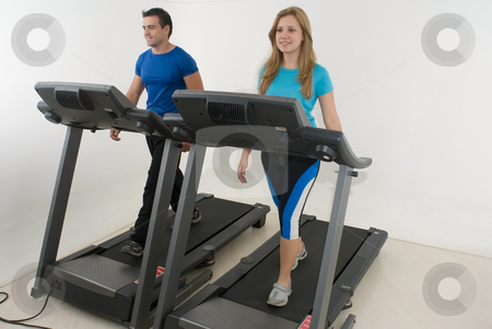 Couple at the Gym - Horizontal stock photo, Attractive young couple working out together at the gym on treadmills. Horizontally framed shot with the couple facing directly ahead by Orange Line Media