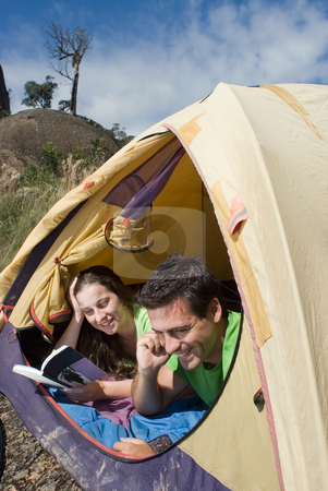 Couple Camping in Tent, Reading and Talking stock photo, Young smiling couple lying in a tent reading a book and talking on a cellphone. by Orange Line Media