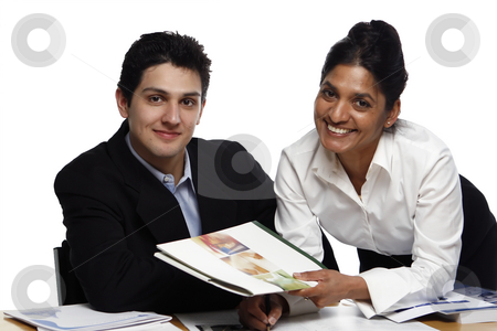 Teamwork - Handing stock photo, Businesswoman standing helping her male colleague who's seated.  Both are looking at the camera.  Shot horizontal isolated on white. by Orange Line Media