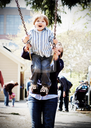 Mother, Son and a Swingset 2 stock photo, Young boy being pushed high on a swing by his mother. Shot is focused on the boy at the start of his swing with the mother visible in the background. Vertical, high-contrast shot. by Orange Line Media