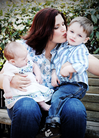 Mother and Children stock photo, Beautiful mother sitting on a park bench with her daughter and son on her lap. She's planting a kiss on her son's cheek. Vertically framed shot. by Orange Line Media