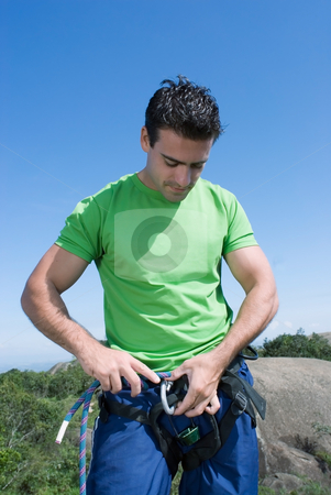 Man Checking Climbing Harness - Vertical stock photo, Athletic young climber checking his gear and climbing harness. Vertical shot set against a blue sky. by Orange Line Media