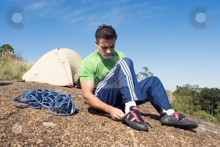 Man Putting on Climbing Shoes - Horizontal stock photo, Attractive young man putting on his rock-climbing shoes in front of his tent by Orange Line Media