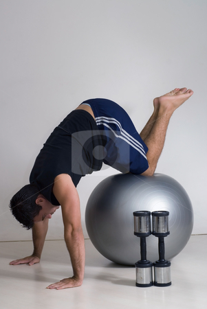 Pushup on Balance Ball - Vertical, Isolated stock photo, Male athelete / weighlifter, with his knees on a balance ball, doing a pushup. by Orange Line Media
