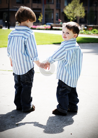 Brothers Holding Hands stock photo, Two identically dressed brothers holding hands in a park. High-contrast style by Orange Line Media