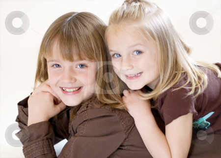 Two Sisters Posing - Horizontal stock photo, Two cute young sisters posing together in a studio. Horizontally framed shot isolated against a white studio background. by Orange Line Media