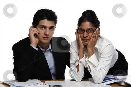 Teamwork - Frustrated stock photo, Frustrated businessman and businesswoman, at a desk, looking at the camera.  Shot horizontal isolated on white. by Orange Line Media