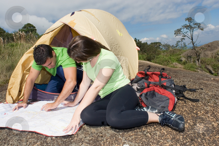 Couple Checking a Map - Horizontal stock photo, Young couple checking their route on a map in front of their tent with ominous gray clouds gathering overhead. Horizontally framed shot. by Orange Line Media