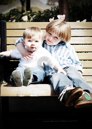 Brothers stock photo, Adorable young brothers sitting together on a park bench on a sunny day by Orange Line Media