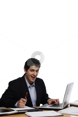 Businessman Looking at You, Suprised stock photo, Businessman, sitting at a desk, writing and smiling at the camera.  Vertical isolated on white. by Orange Line Media