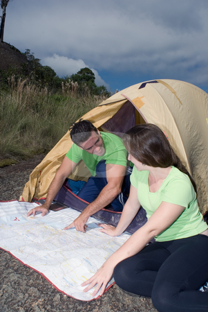 Couple Checking a Map stock photo, Young couple checking their route on a map in front of their tent with ominous gray clouds gathering overhead by Orange Line Media