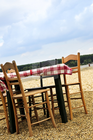Dining table in a beach stock photo, Dining table and chairs set outside on a beach by Elena Elisseeva