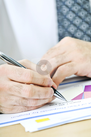 Office worker writing on reports stock photo, Office worker reviewing generic presentation charts and reports by Elena Elisseeva
