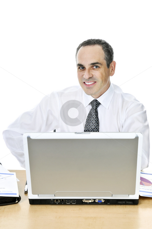 Businessman at his desk on white background stock photo, Happy businessman sitting at his desk isolated on white background by Elena Elisseeva