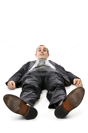 Businessman laying down on white background stock photo, Scared businessman laying down in a suit isolated on white background by Elena Elisseeva
