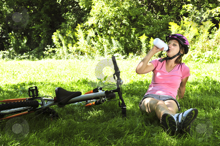 Teenage girl resting in a park with a bicycle stock photo, Teenage girl resting in a park with a bicycle drinking water by Elena Elisseeva