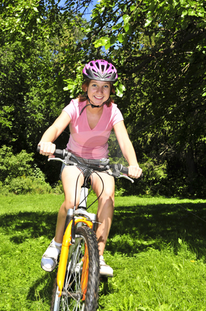 Teenage girl on a bicycle stock photo, Portrait of a teenage girl riding a bicycle in summer park outdoors by Elena Elisseeva
