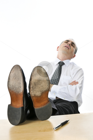 Sleeping businessman stock photo, Sleeping businessman with feet up on his desk by Elena Elisseeva