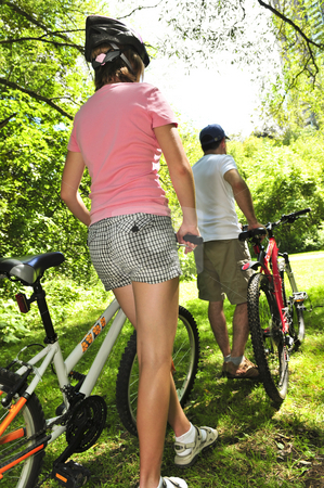 Family on bicycles stock photo, Teenage girl and her father with bicycles in summer park by Elena Elisseeva
