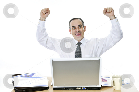 Businessman at his desk on white background stock photo, Happy businessman raising his arms sitting at his desk isolated on white background by Elena Elisseeva