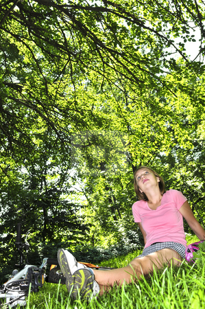 Teenage girl relaxing in a park with her bicycle stock photo, Teenage girl relaxing under green tree with her bicycle by Elena Elisseeva