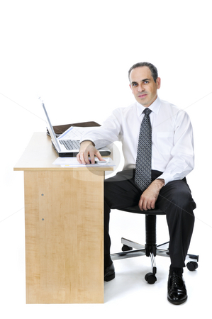 Businessman at his desk on white background stock photo, Serious businessman sitting at his desk isolated on white background by Elena Elisseeva